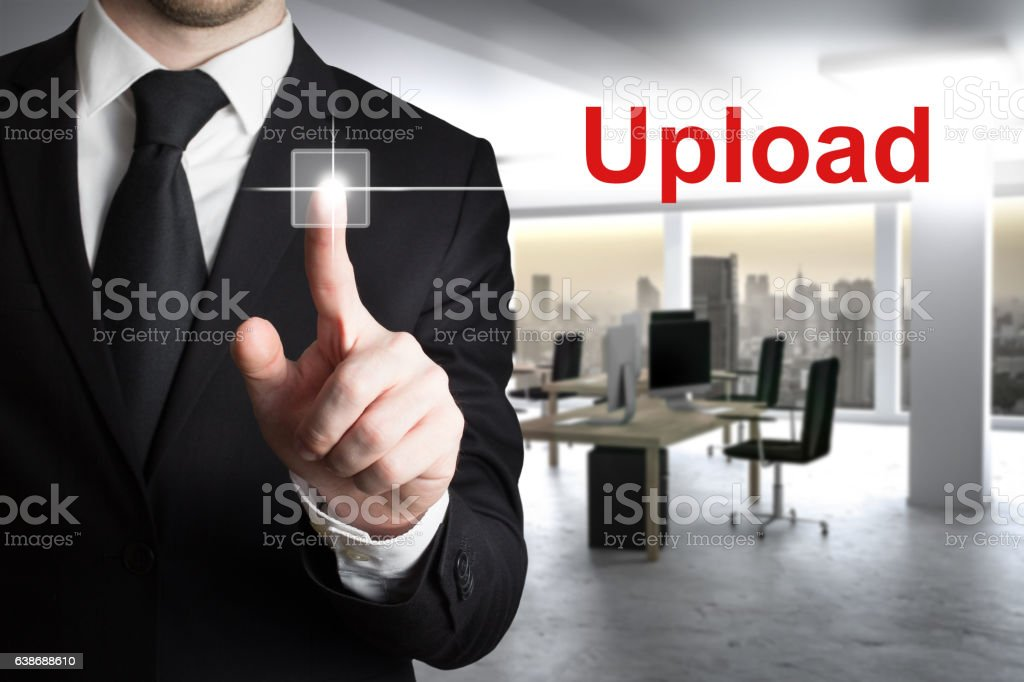 businessman in modern office pushing button upload stock photo