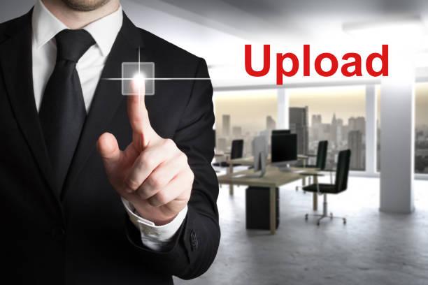 businessman in modern office pushing button upload - kostenlose onlinespiele stock-fotos und bilder