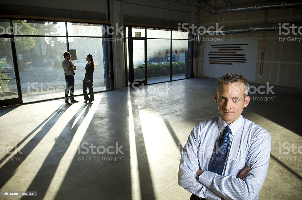 Businessman in office, colleagues in background royalty free stockfoto