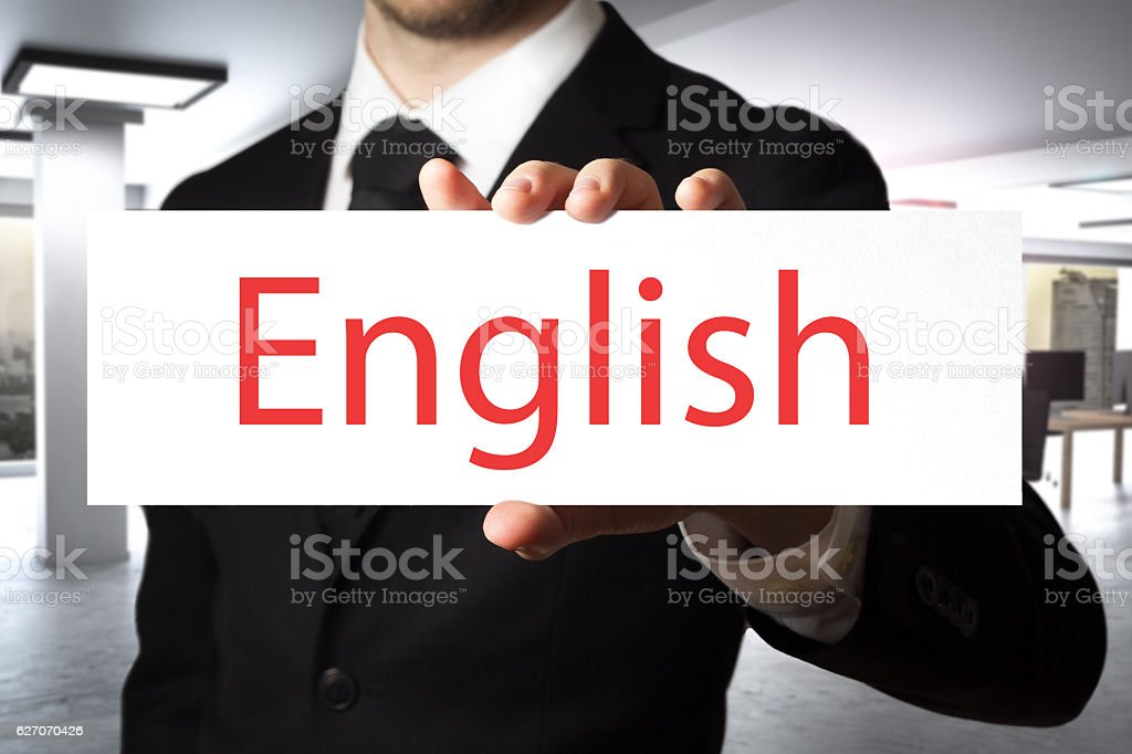 businessman in office holding sign english stock photo