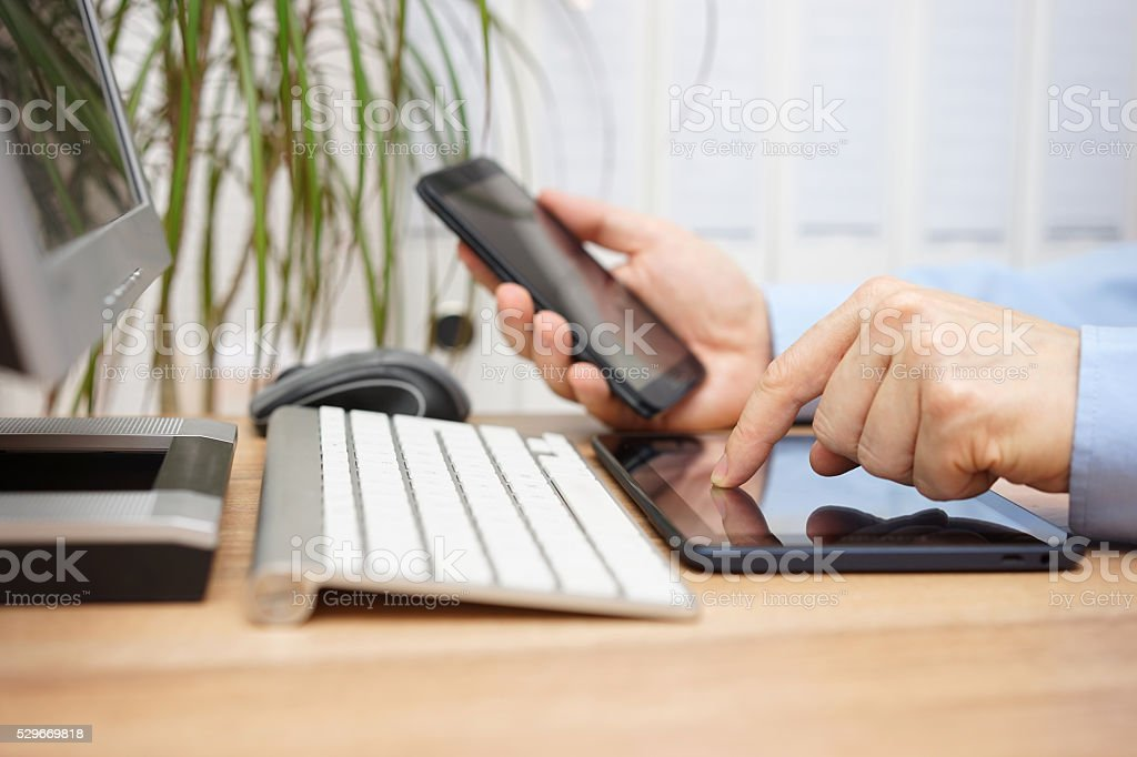 businessman in office is using computer,tablet and smart mobile stock photo