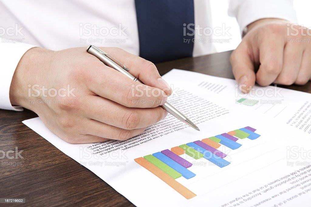 businessman in office of table points to the graphics royalty-free stock photo