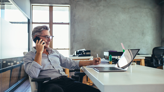 Businessman on the phone sitting at the laptop in his office. Male business professional in office talking on cell phone.
