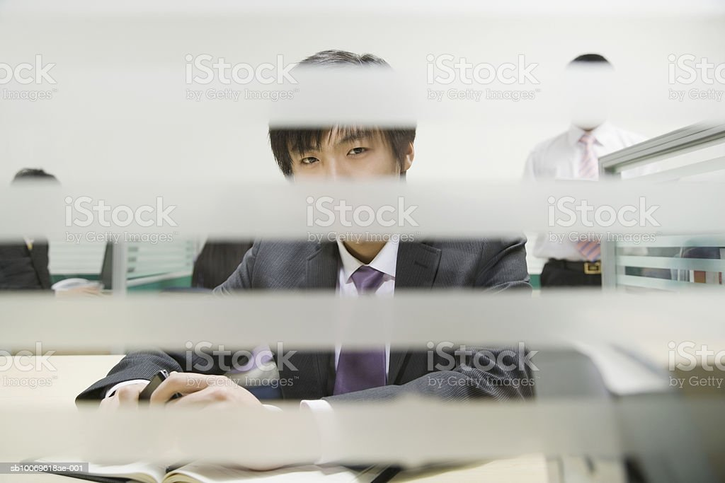 Businessman in office, view through window blinds foto de stock libre de derechos