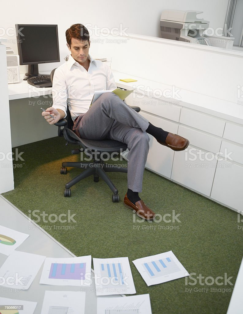 Businessman in office with charts on the floor 免版稅 stock photo