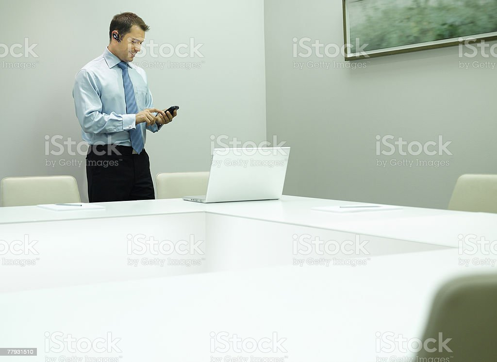 Businessman in office with mobile phone and earpiece royalty-free stock photo