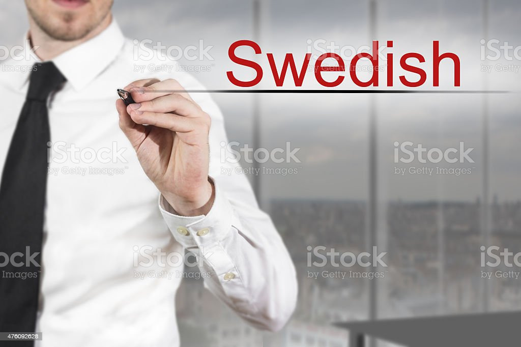 businessman in office writing swedish in the air stock photo