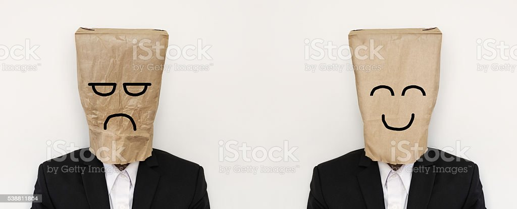 Businessman in paper bag with anger and smile face stock photo
