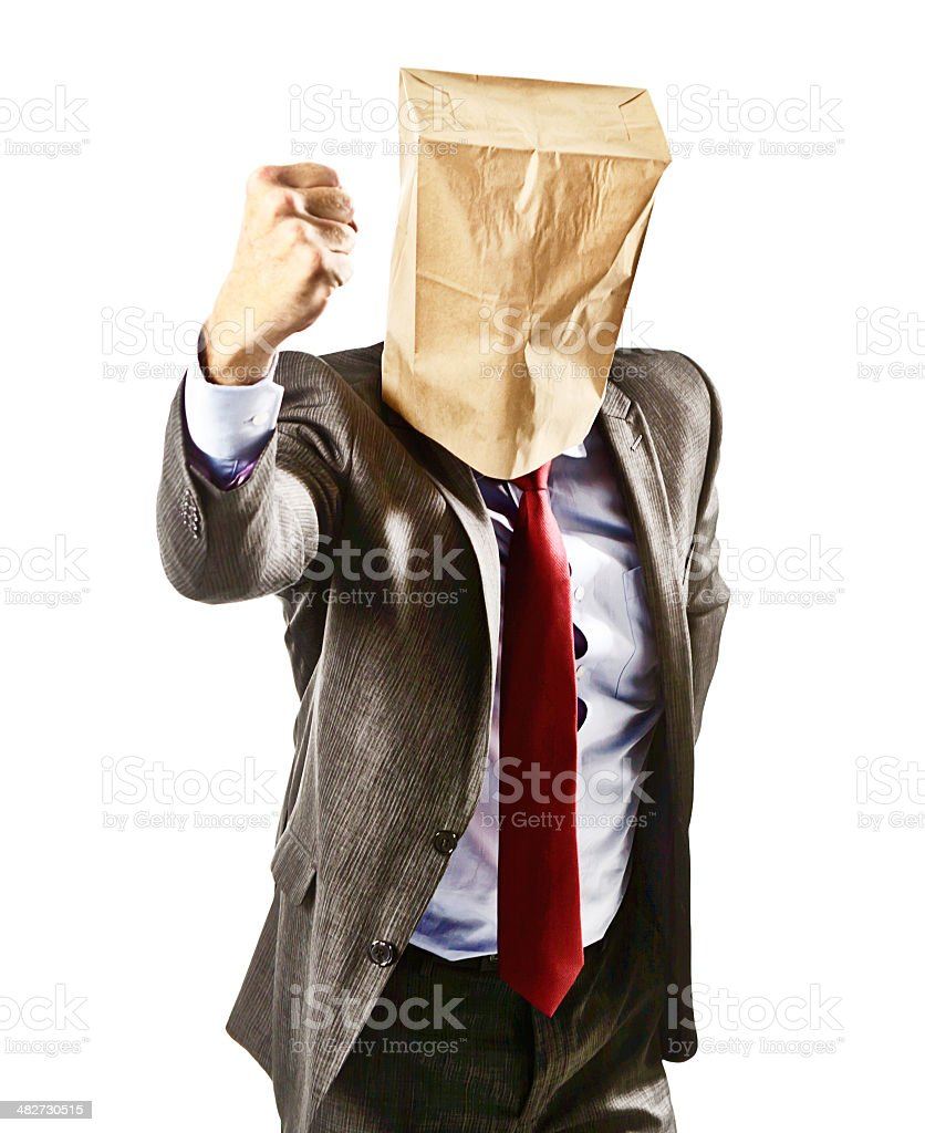 Businessman in paper-bag mask shakes his fist angrily, threatening someone stock photo