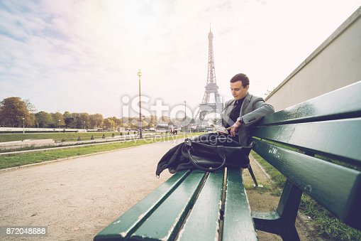 istock Businessman in Paris reading a book, Eiffel Tower 872048688