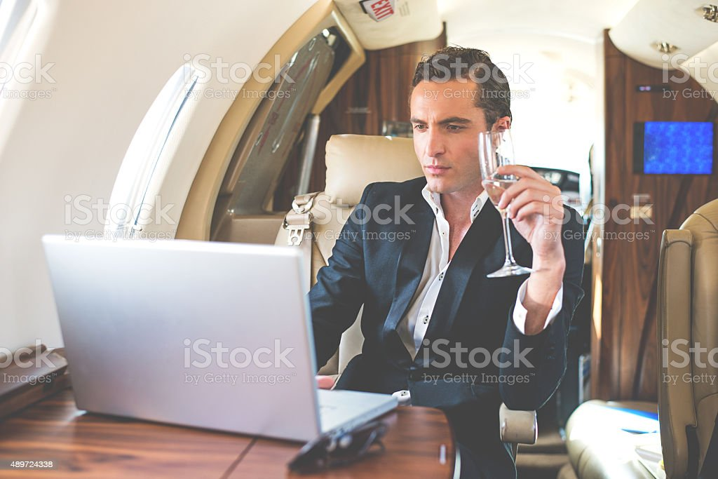 Businessman in private jet drinking champagne stock photo