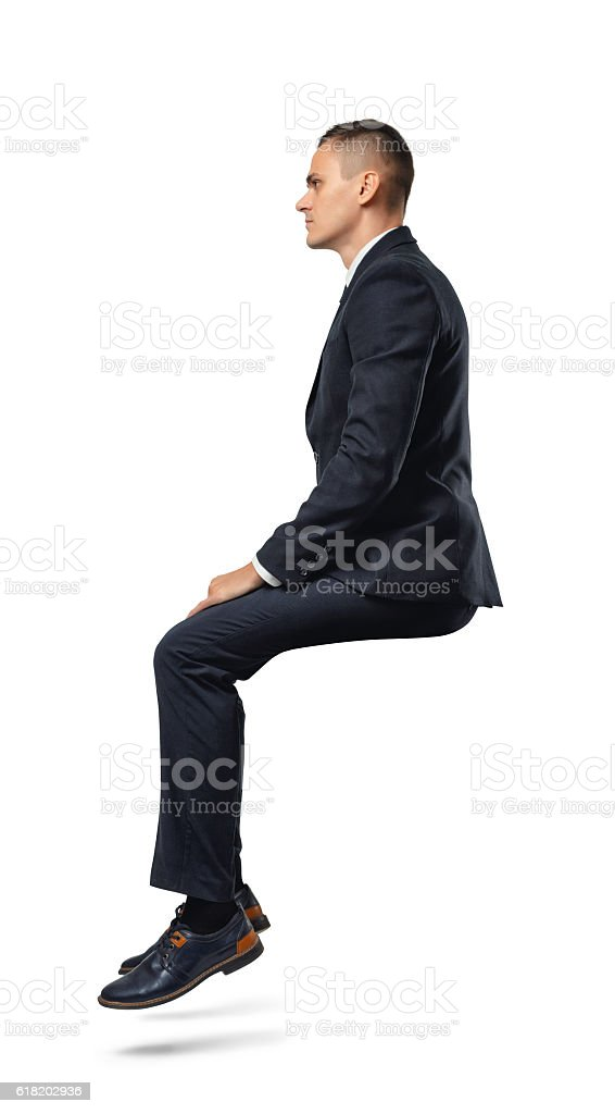 Businessman in profile in sitting position isolated on the white stock photo