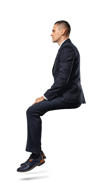 Businessman in profile in sitting position isolated on the white 스톡 사진