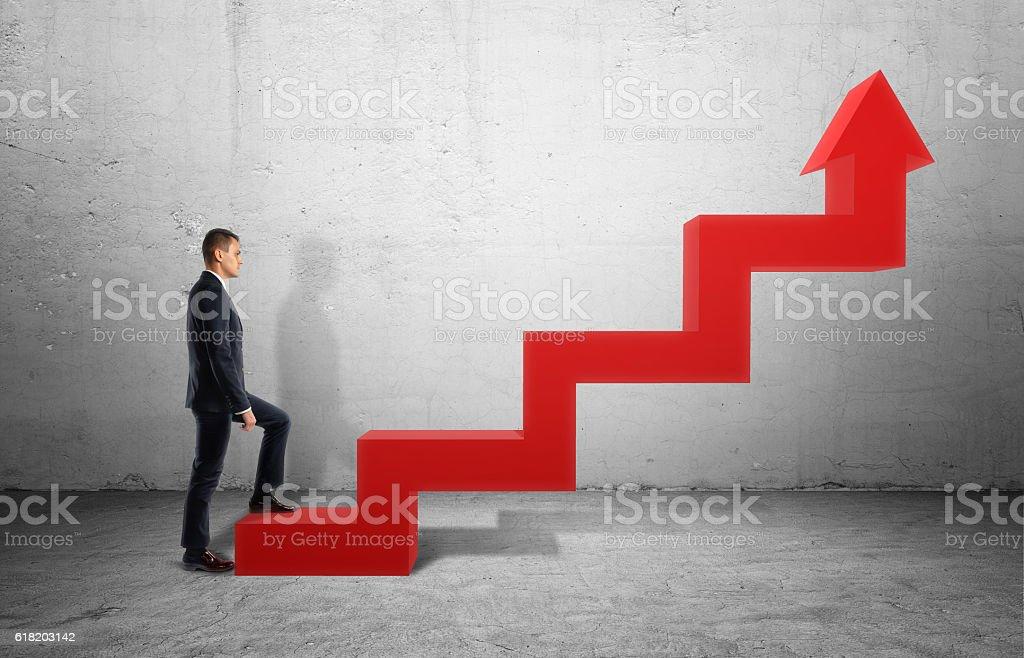 Businessman in profile walking up big red arrow in form - foto de acervo