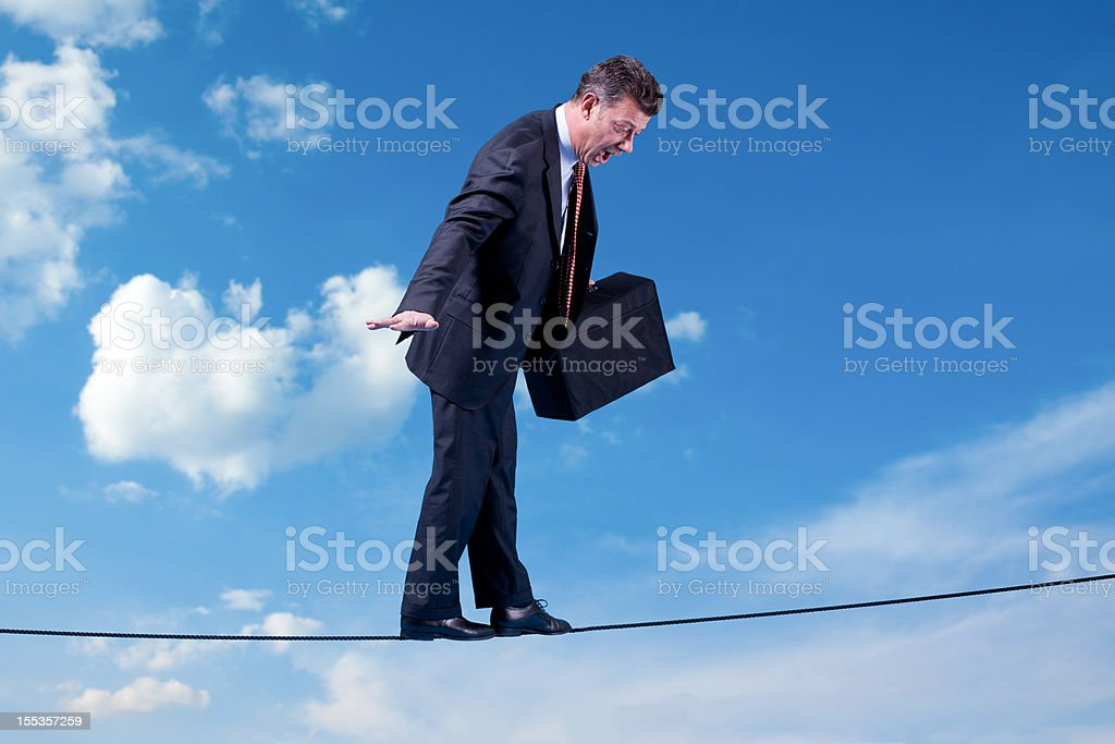Businessman in Risky Situation Looking Down royalty-free stock photo