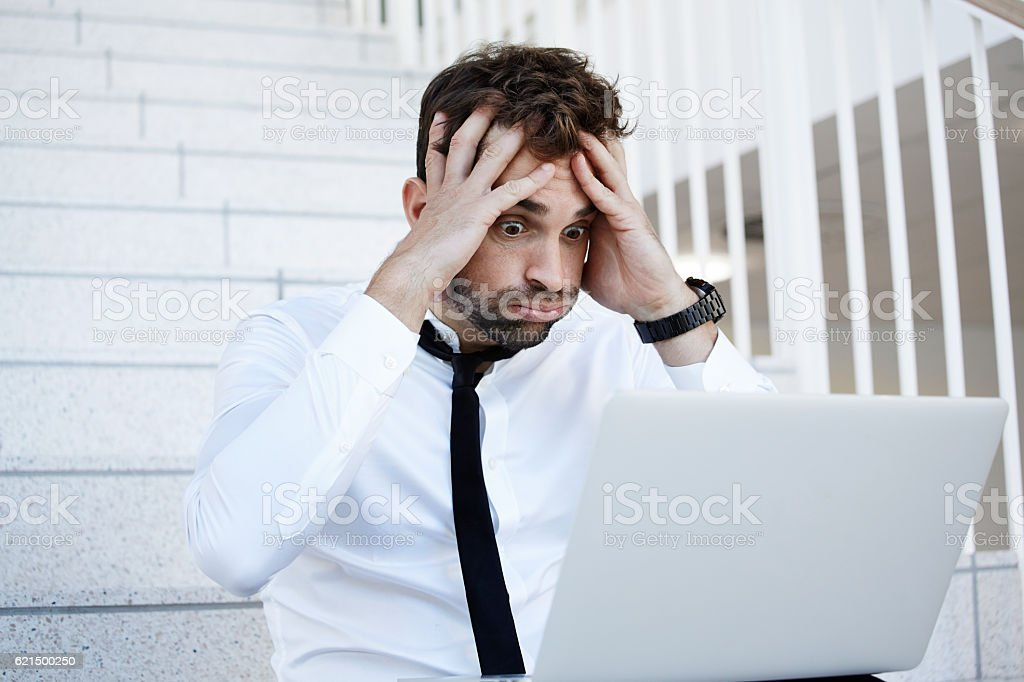 Businessman in shock at laptop stock photo