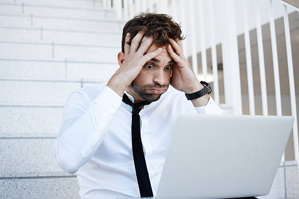 Businessman in shock at laptop Businessman in shock at laptop head in hands stock pictures, royalty-free photos & images