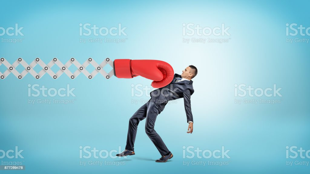 A businessman in side view gets hit with a large red boxing glove attached to a metal scissor arm on a blue background. stock photo