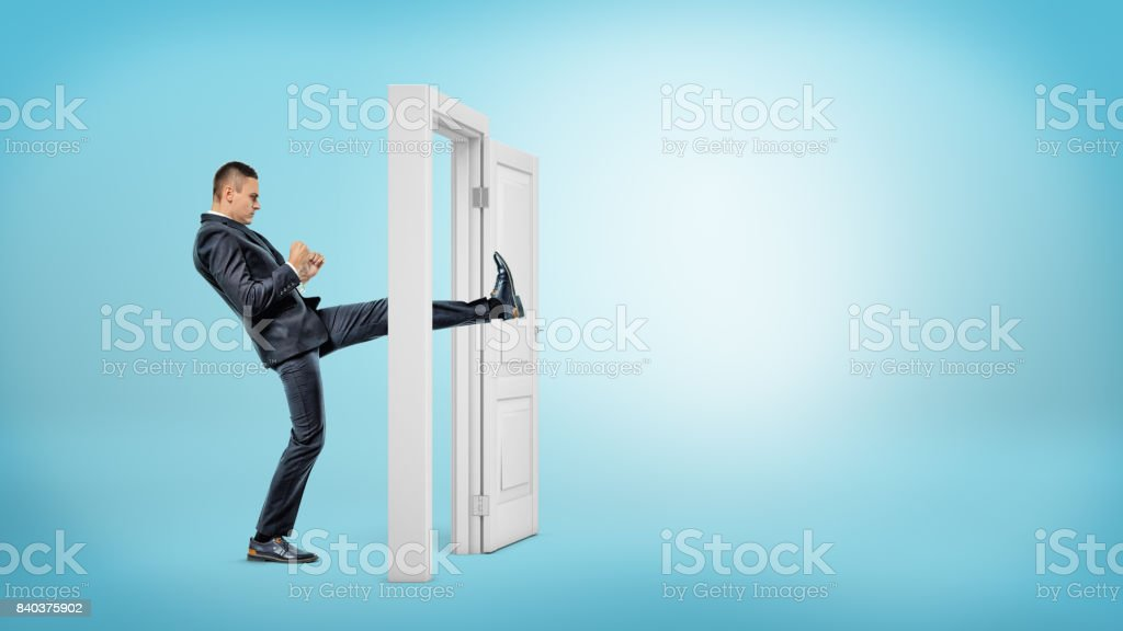 A businessman in side view kicks a small white door open with his leg on blue backgrounds stock photo