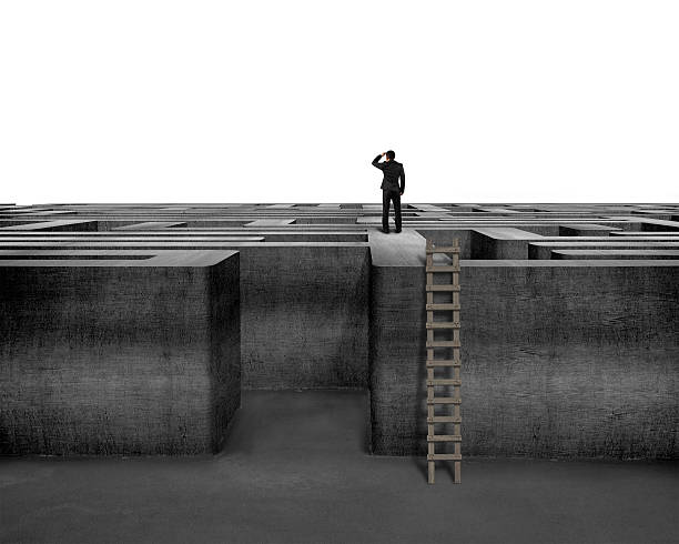 Businessman in silhouette atop a concrete maze stock photo