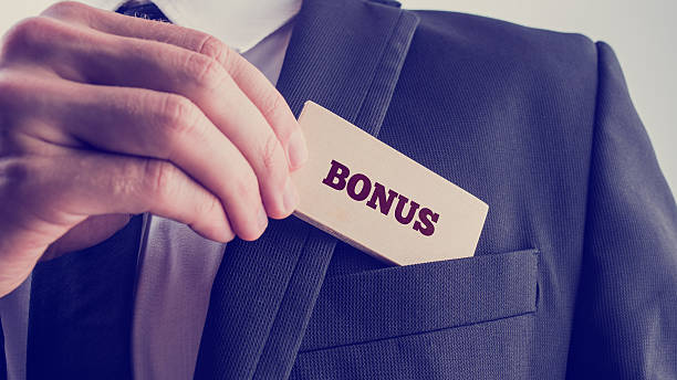Businessman in Simple Bonus Concept Close up Businessman in Black Suit Putting Small Wooden Piece with Bonus Text to Front Pocket. A Simple Company Bonus Concept. perks stock pictures, royalty-free photos & images