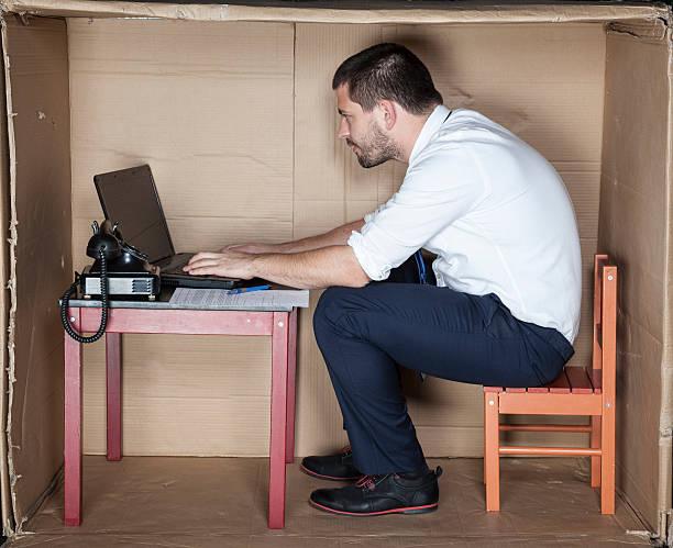 geschäftsmann in einem kleinen büro arbeiten auf laptop - sachenmacher stock-fotos und bilder