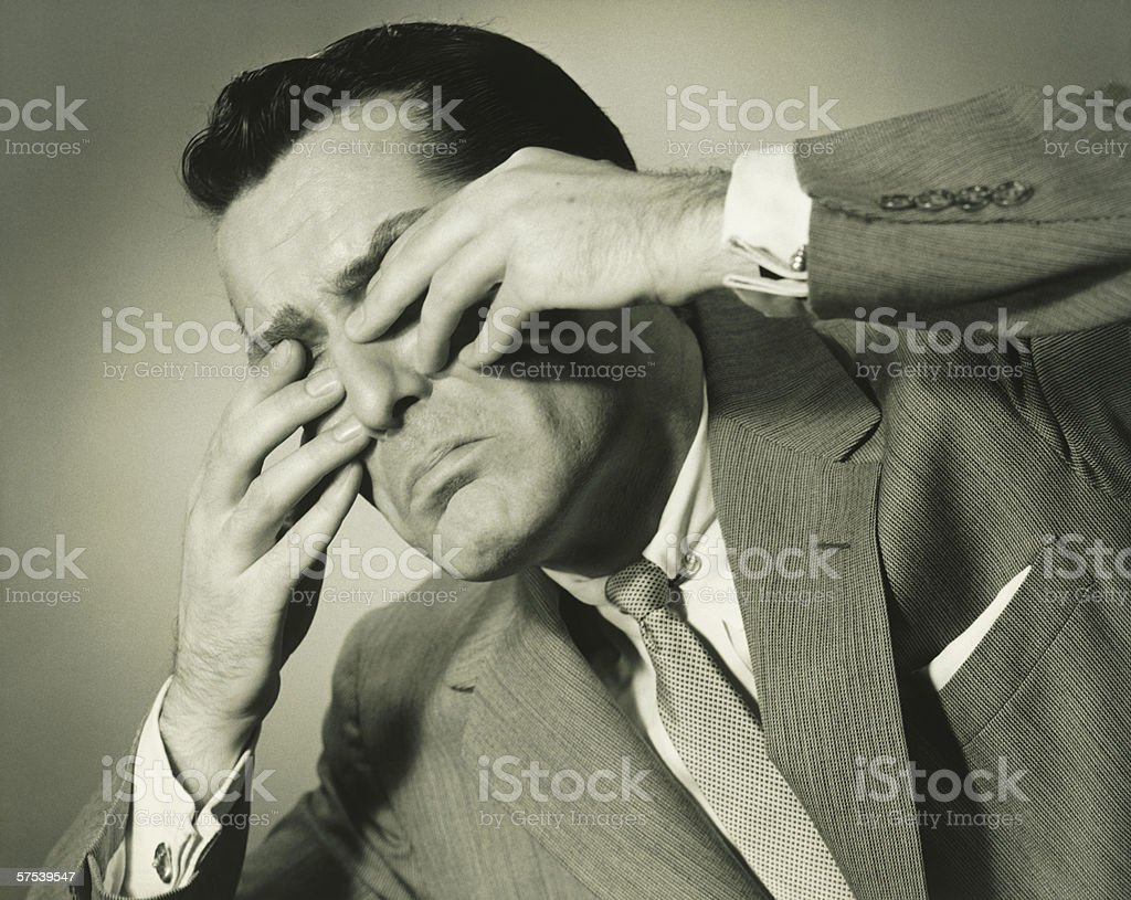 Businessman in studio covering eyes with fingers, (B&W), close-up royalty-free stock photo