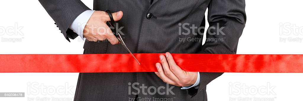 Businessman in suit cutting red ribbon with pair of scissors stock photo