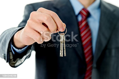 Businessman in suit handing key