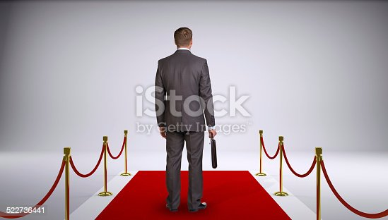 istock Businessman in suit holding briefcase and standing on red carpet. 522736441