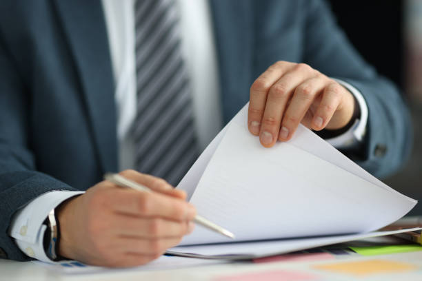 Businessman in suit holding documents in his hands in office closeup stock photo