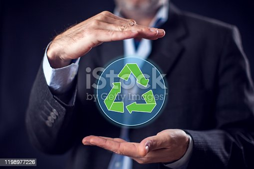 Businessman in suit holding in hands virtual sign of recycling. Ecology and environmental protection concept