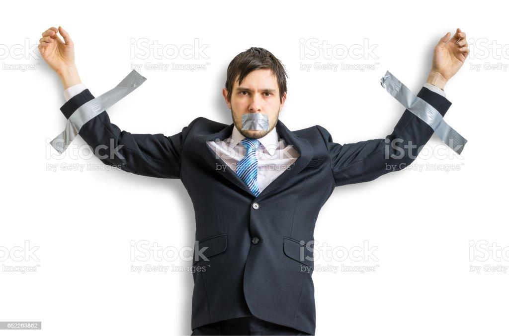Geschäftsmann im Anzug ist an der Wand mit Klebeband abgeklebt. Isoliert auf weißem Hintergrund. – Foto