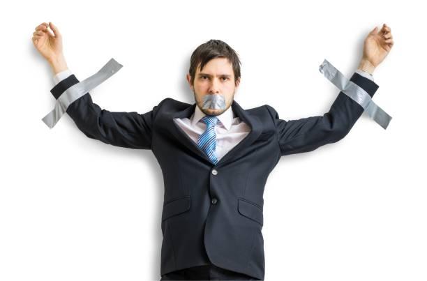 Hombre de negocios en traje es pegada a la pared con cinta adhesiva. Aislado sobre fondo blanco. - foto de stock