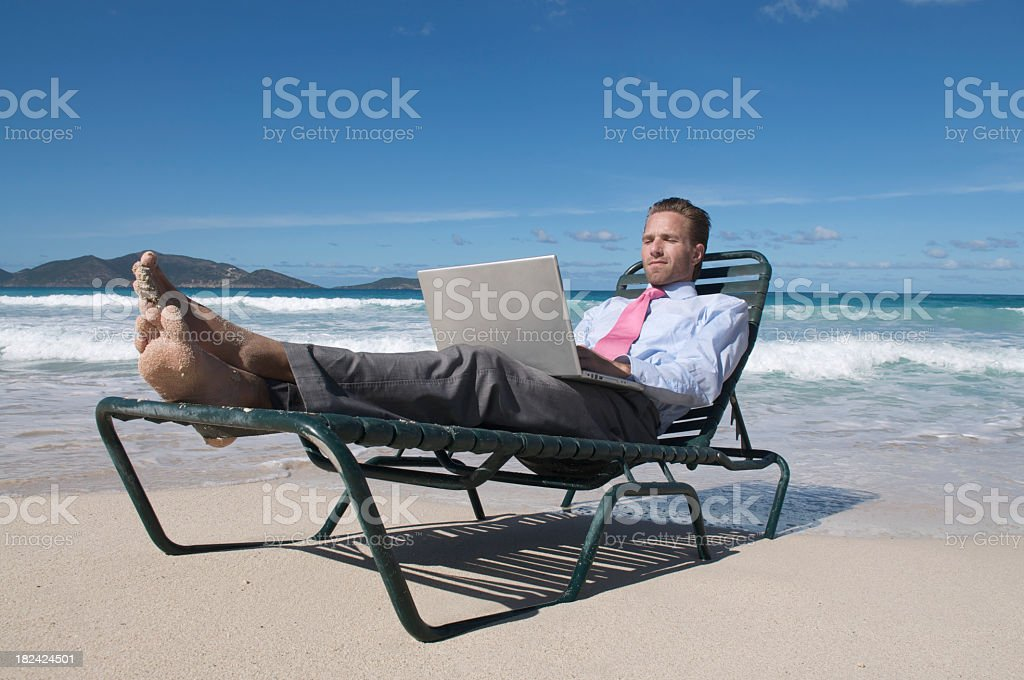 Businessman in suit on lounge with laptop at beach stock photo