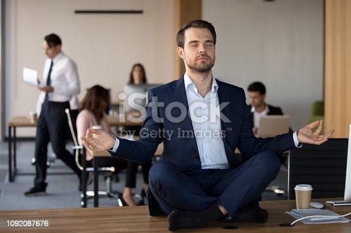 istock Businessman in suit sitting on table and meditating in office 1092087676