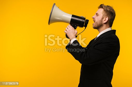istock businessman in suit speaking to megaphone over yellow background - Image 1137392579