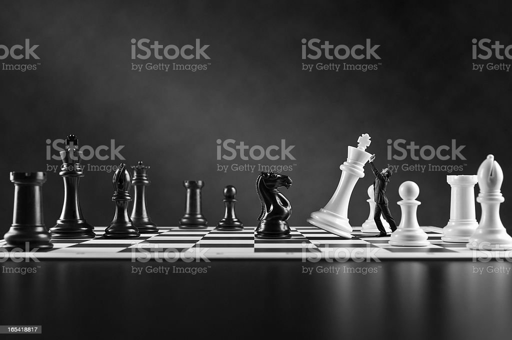 Businessman in suit supporting falling white Chess King, Chess board stock photo