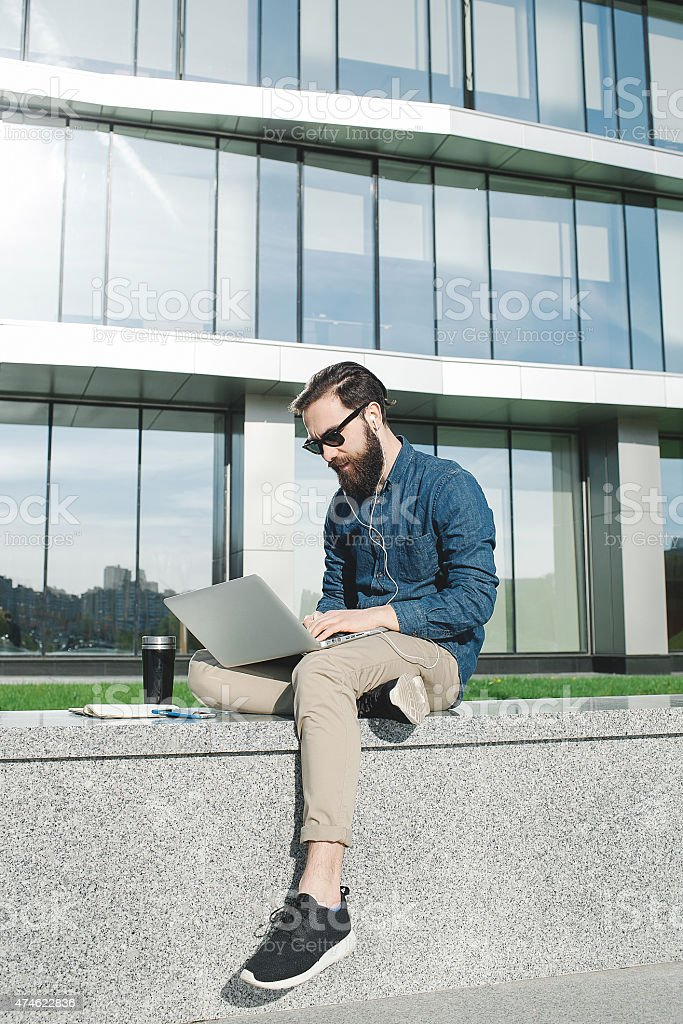 Businessman in sunglasses with laptop outdoors in front of office stock photo