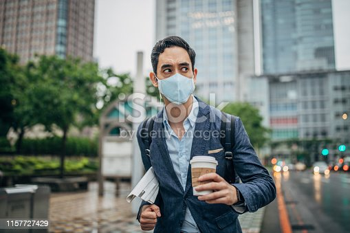 Businessman wearing surgical mask to protect from flu/air pollution in city.
