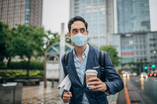 Businessman in the city Businessman wearing surgical mask to protect from flu/air pollution in city. epidemic stock pictures, royalty-free photos & images