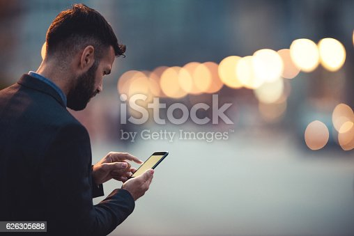 Side view of a young businessman texting on the cellphone.