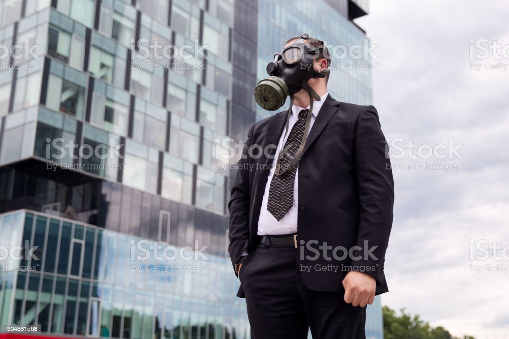 Businessman in the city wearing a gas mask on the face. stock photo