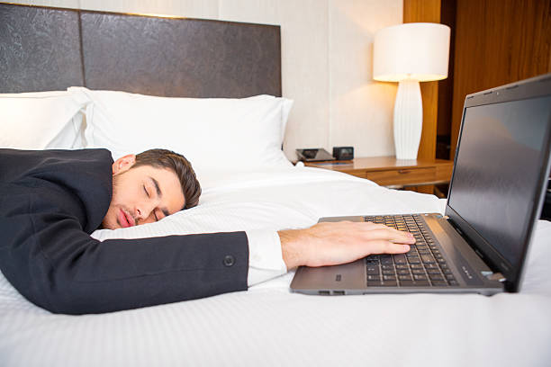 Businessman in the luxury hotel Tired and overworked. Exhausted business man in formalwear sleeping on the bed of the luxury hotel room keeping his hand on laptop keyboard jet lag stock pictures, royalty-free photos & images