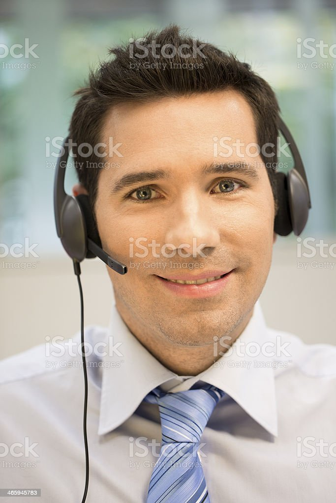 Businessman in the office on phone with headset stock photo