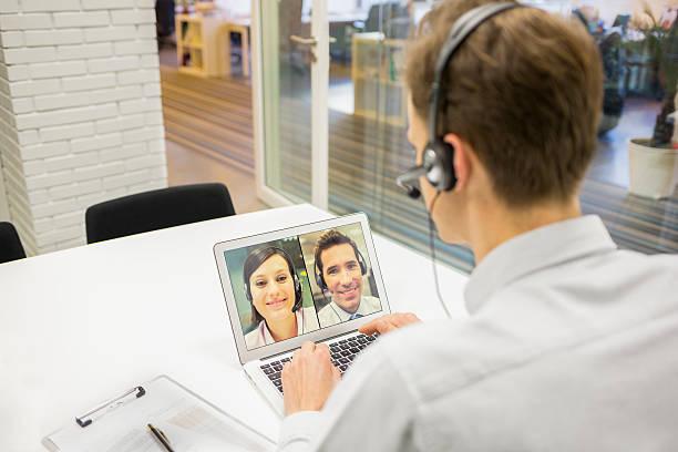 uomo d'affari in ufficio con cuffia in videoconferenza, skype - video call foto e immagini stock