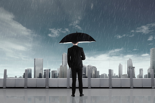 Businessman in the rain with umbrella