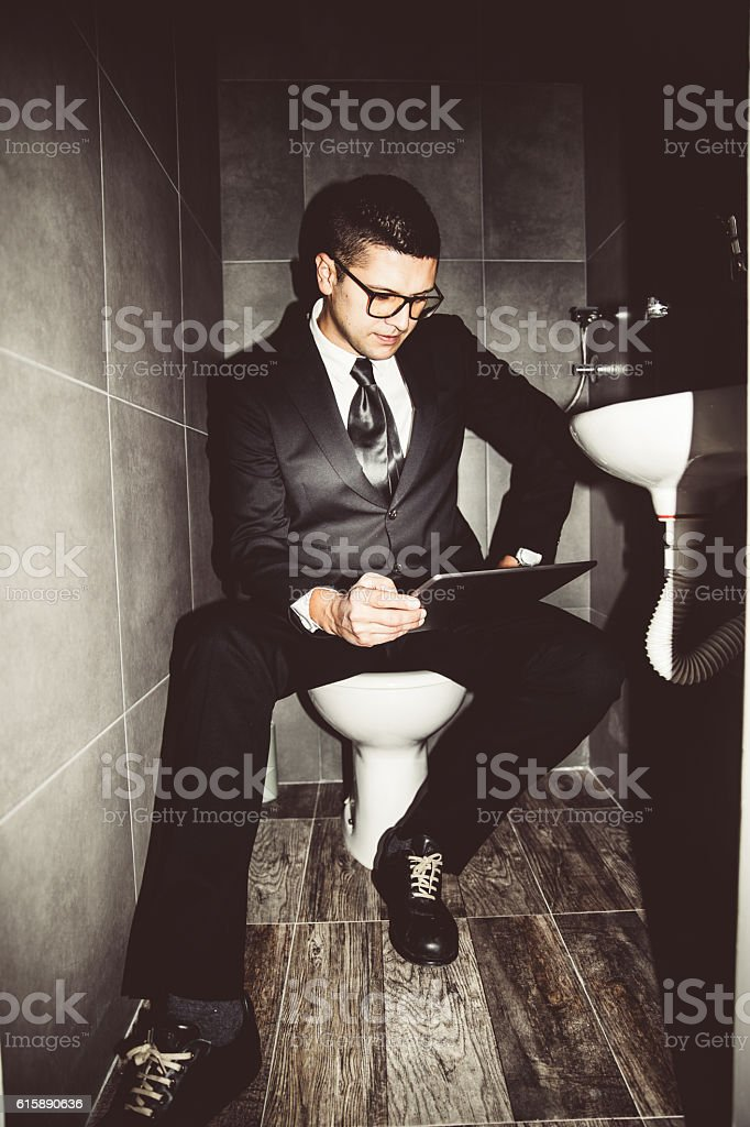 Businessman in the restroom stock photo