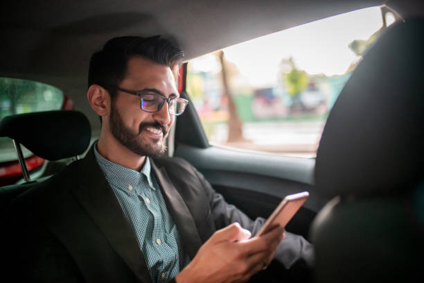 Businessman in the taxi, using a mobile phone stock photo