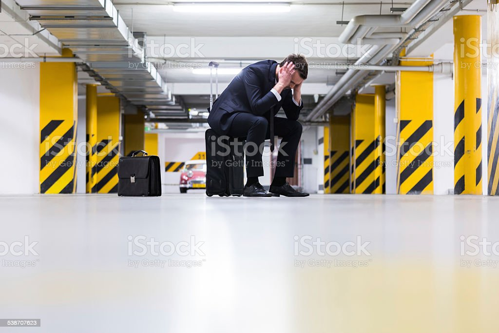 Businessman in underground garage Full lenght portrait of disappointed businesswoman sitting on the suitcase in the underground parking. 2015 Stock Photo